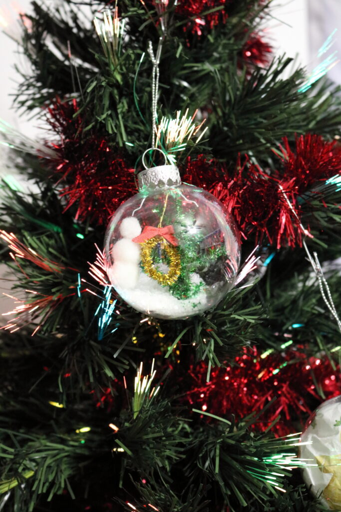 clear christmas ornament idea winter scene with snowman, tree, and wreath