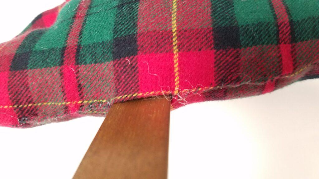 sewing up the seam around the stick