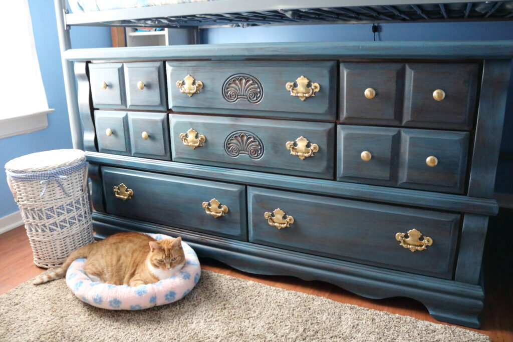 Finished blue dresser with a cat and a white basket