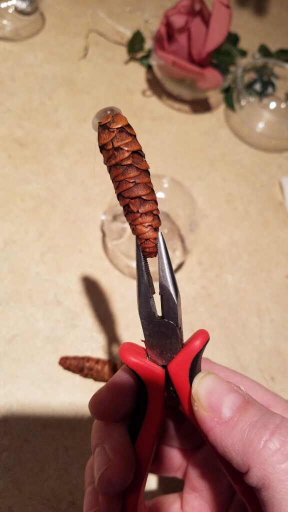 pliers holding pinecone with hot glue on the pine cone