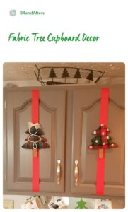 fabric Christmas trees on red ribbon on gray cabinet doors
