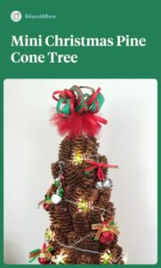 miniature pine cone tree decorated with miniature Christmas ornaments and a cute ribbon topper
