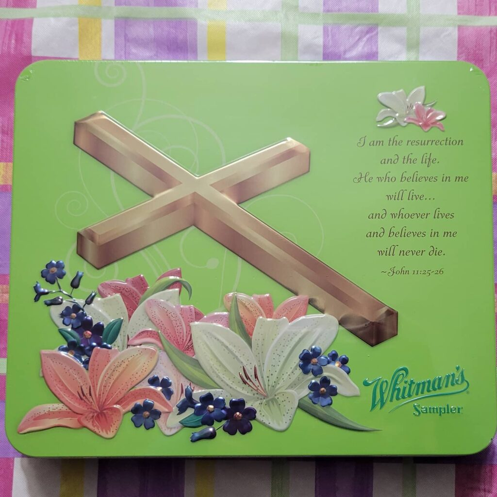 Green Whitman's chocolate tin with cross and Bible verse on it
