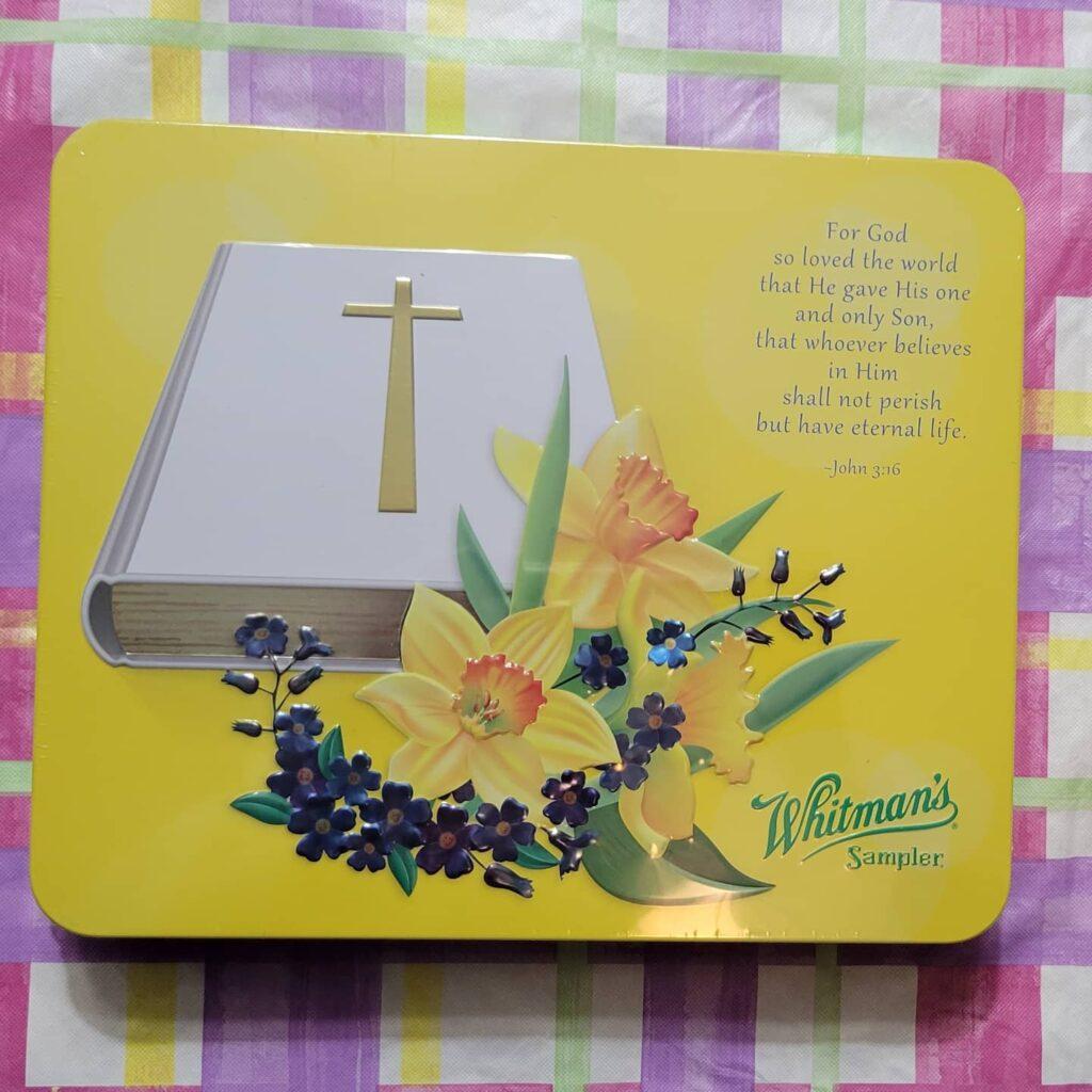 Yellow Whitman's chocolate tin with white Bible and John 3:16 on it