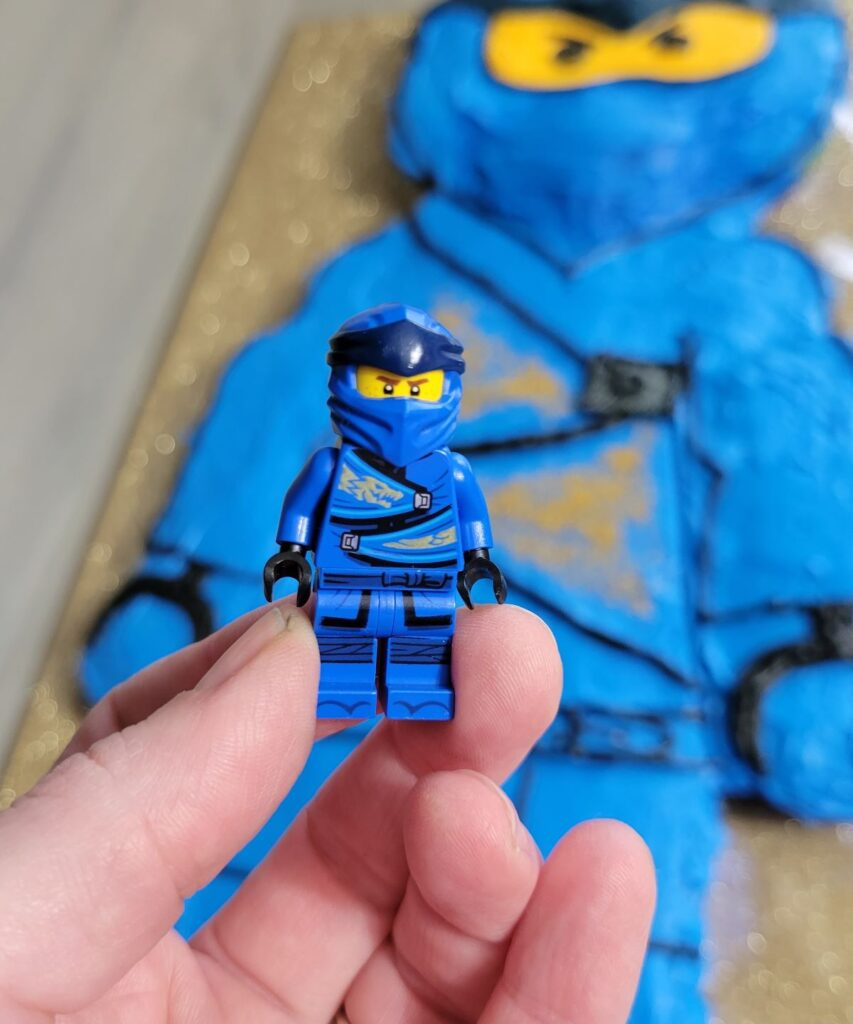 blue minifig with cake in background