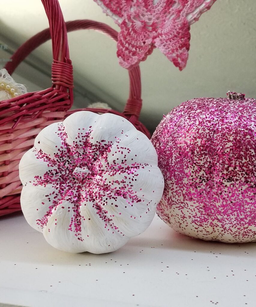 white pumpkins with pink glitter on them