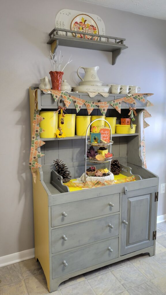 fall decorated hutch with yellow canisters