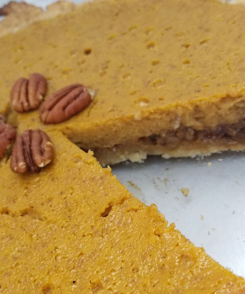 pumpkin pie with slice out of it
