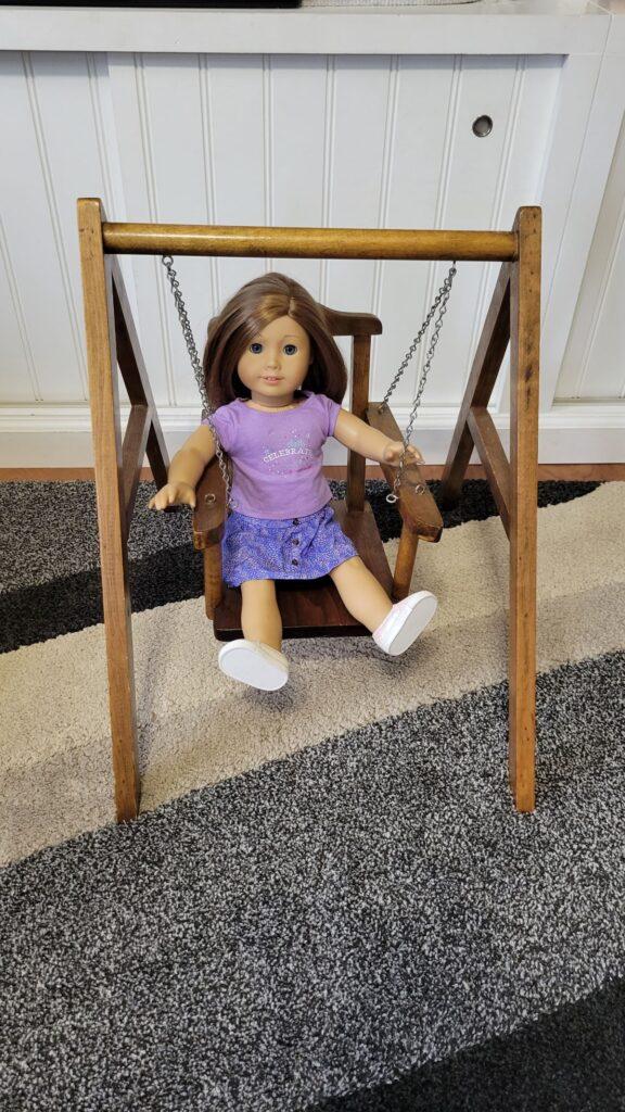 American girl doll in a wooden swing