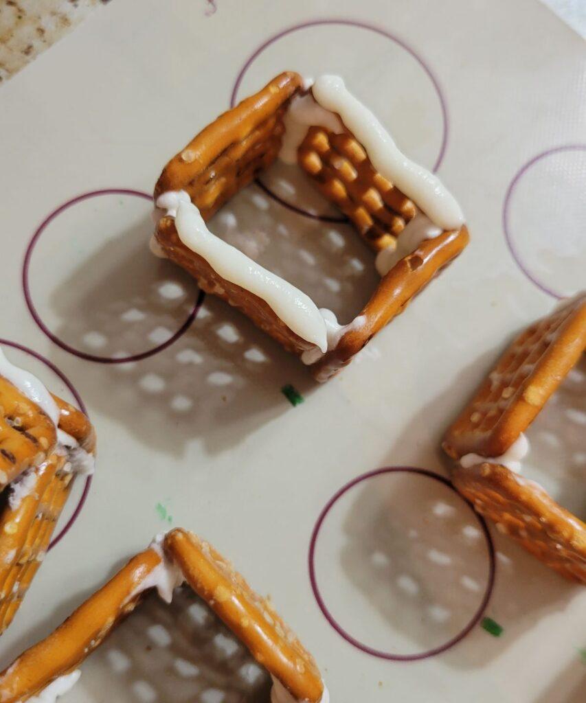 white frosting on square pretzels