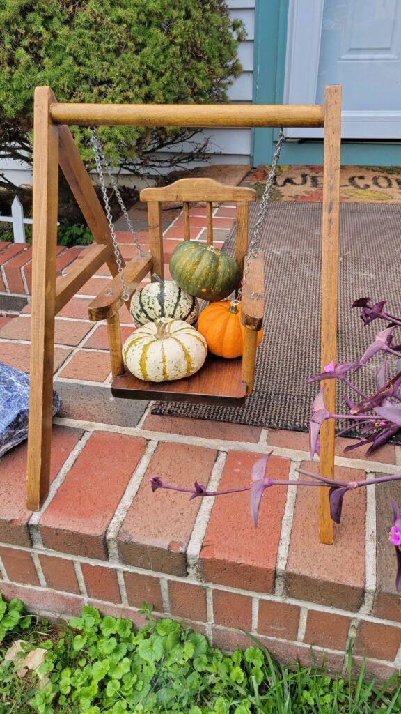 mini pumpkins on a miniature swing
