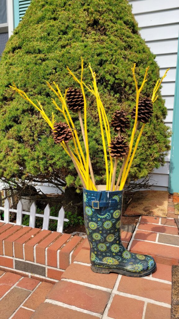 yellow painted dried stems and pine cones in a rain boot