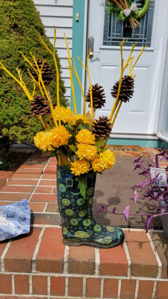 faux yellow flowers, pine cones, dried stems in a rain boot
